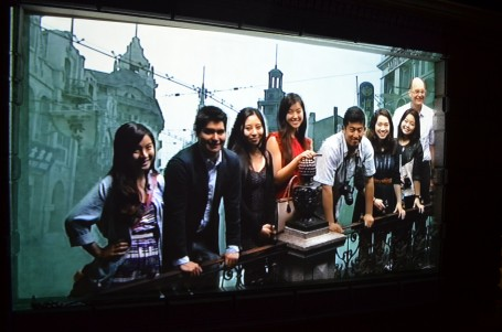 A group of the class poses for a group picture with a shot of old Shanghai in the background.