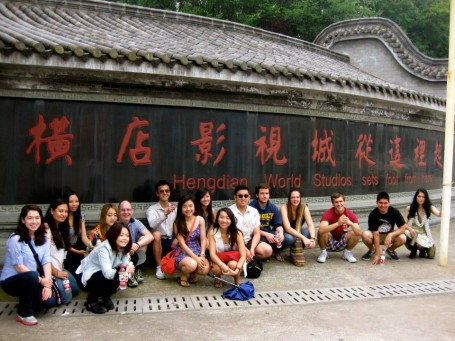 Popping a squat in front of the Hengdian World Studios sign.