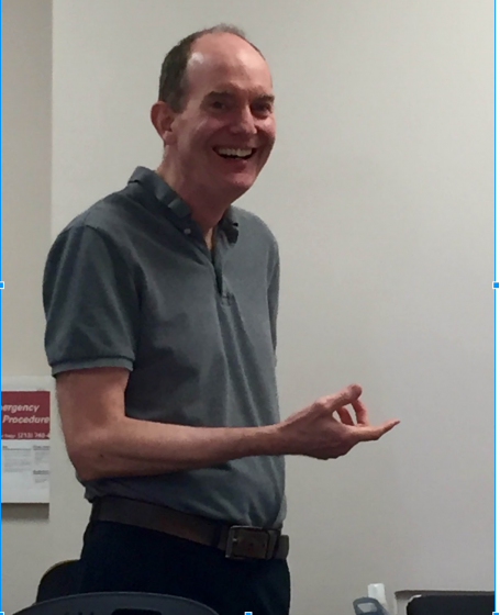 Professor Sheehan lecturing and flashing a smile.