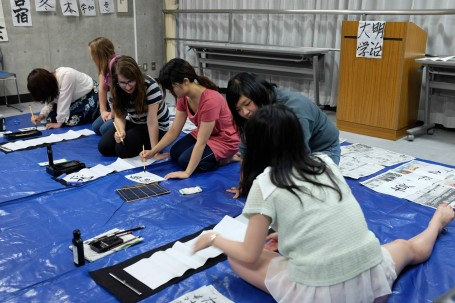 Meiji students teaching the finer skills of Japanese Calligraphy