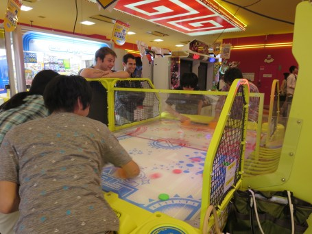 Meiji and USC students playing the intense version of Air Hockey