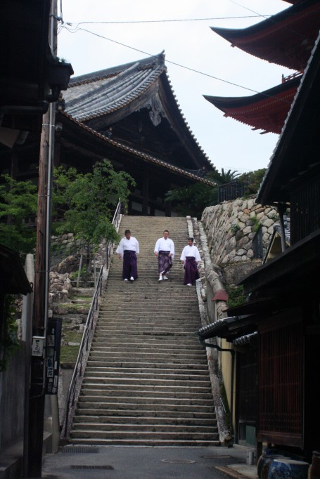 Men in kimonos descending a staircase.