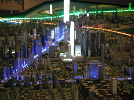 The miniature city is lit up in honor of it's modern architecture and smart planning. The green, orange and blue lights around them are roads leading to this metropolis.