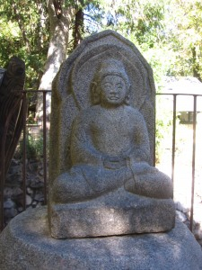 Stone Buddha statue at Tassajara illustrating the cross-legged meditation posture.