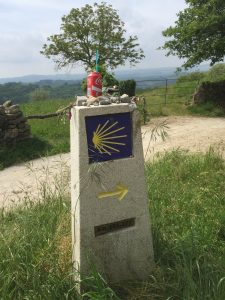 Camino directional and mile marker decorated with stones (prayers left behind), etc.
