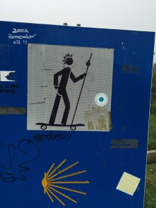 This Camino directional sign has been altered with skateboard and hairdo.